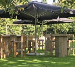 steigerhouten staantafels en krukken in tuin met parasol